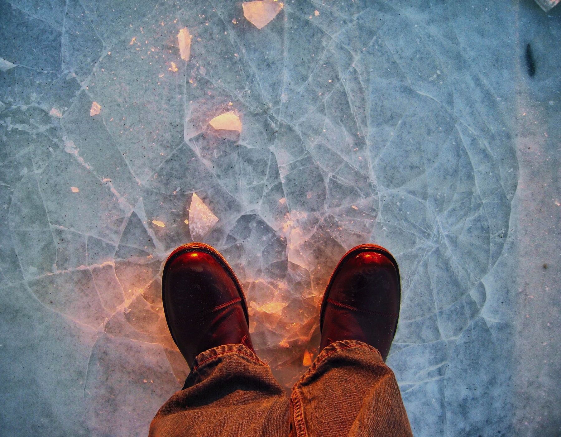 A pair of boots on top of a frozen lake.