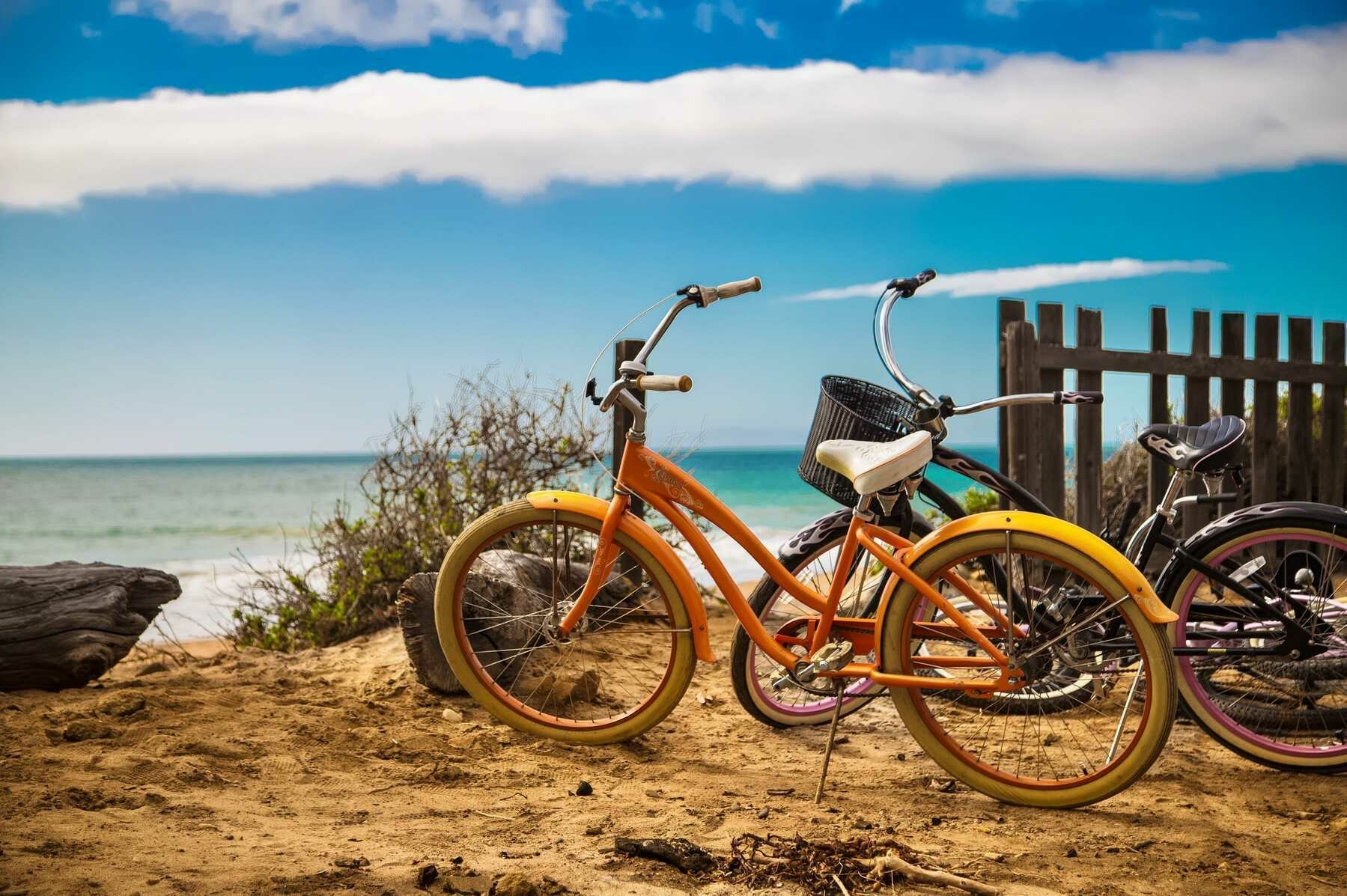 Bicycles resting on a sunny beach.