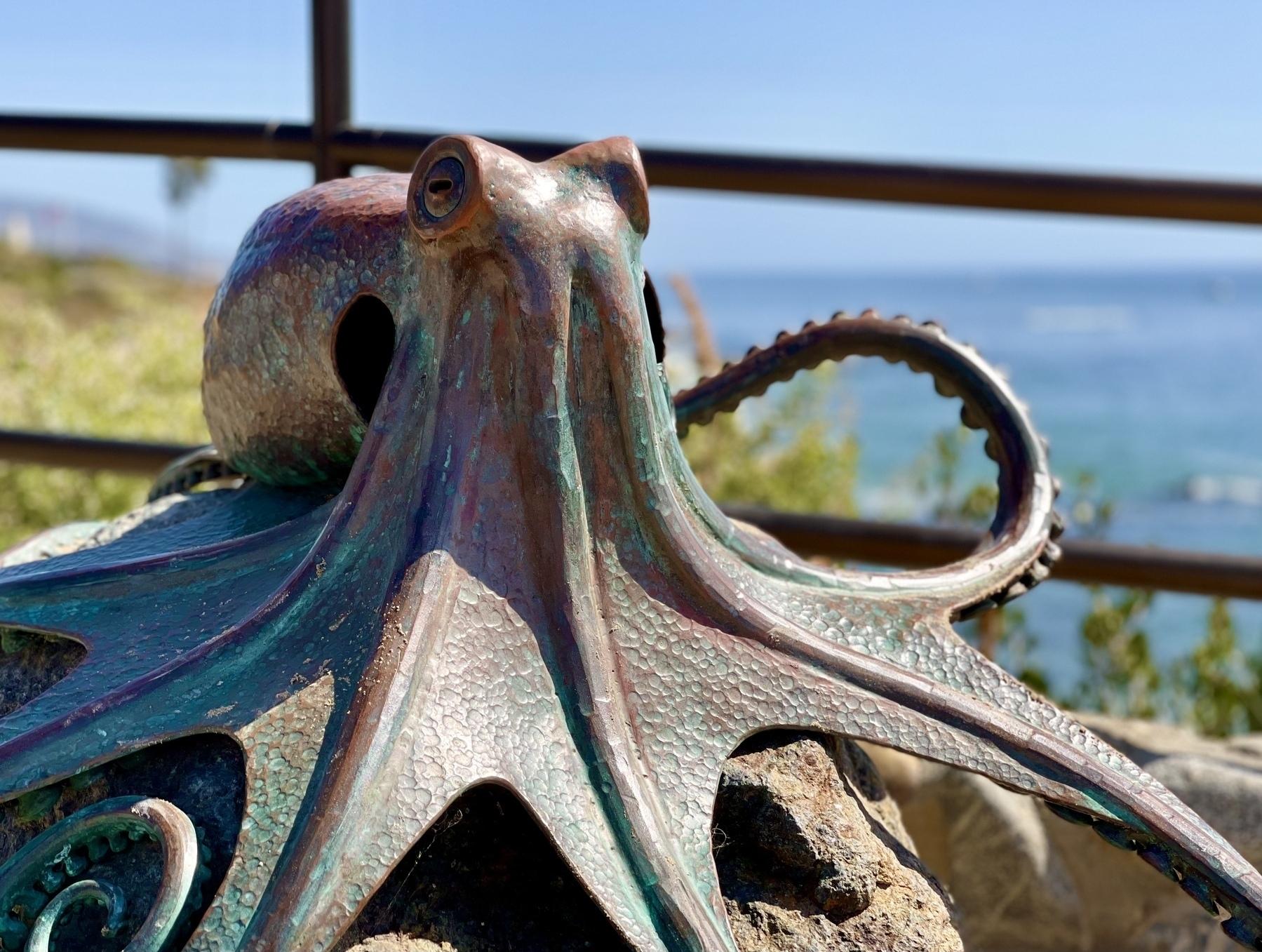 A sculpture of a large kraken at a beach.